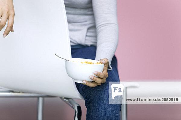 Junge Frau hält Schale mit Cornflakes  beschnitten