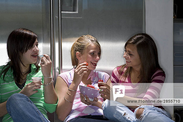 Teen girls laughing and eating