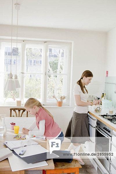 Mädchen und Frau am Tisch sitzend bei der Arbeit