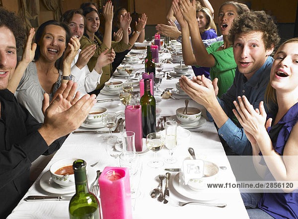 Menschen bei Tisch  klatschende Hände