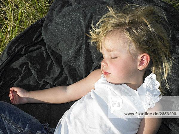 Mädchen schläft auf einem Feld  unter der Sonne