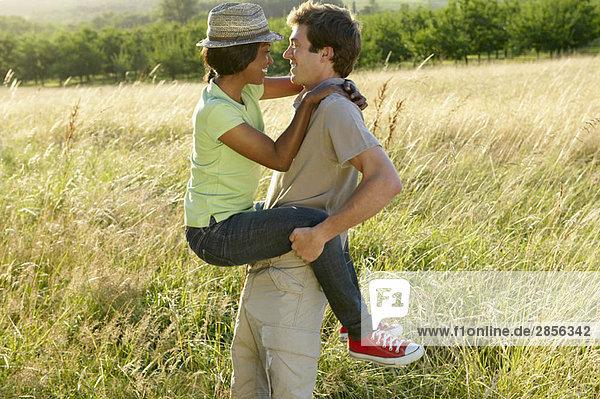Mann trägt seine Frau  auf einem Feld
