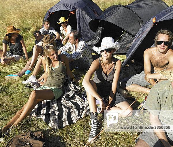 Menschen auf einem Feld  Zelte mit Rucksack