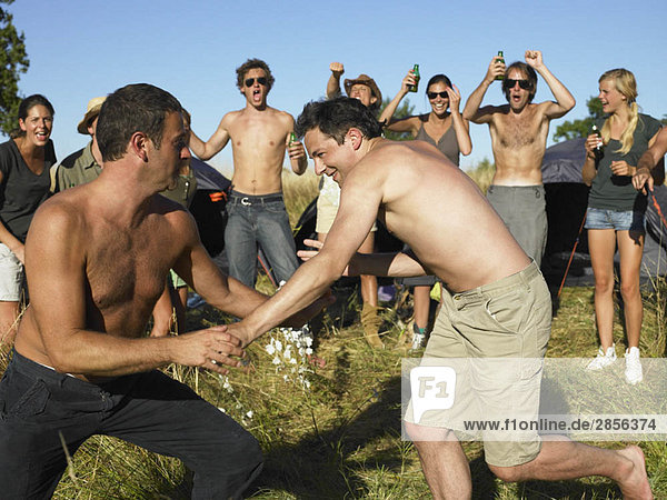 Men fighting  supporting crowd