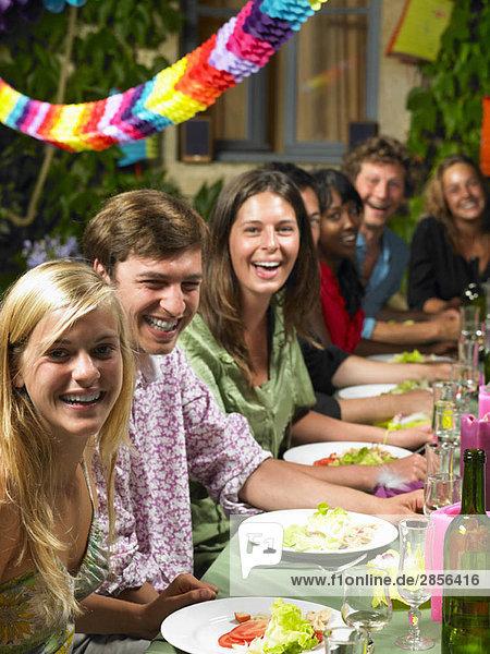 Leute  die am Tisch sitzen und feiern.