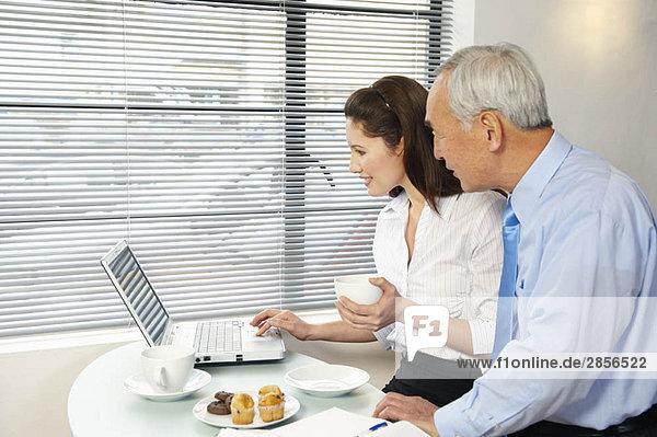Frau und älterer Mann auf dem Laptop