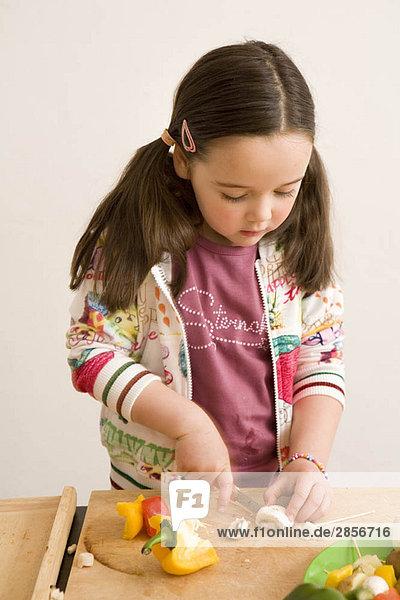 Mädchen beim Schneiden von Gemüse