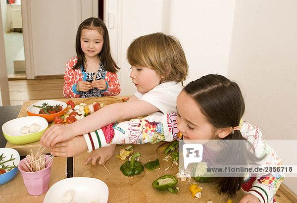 Zwei Mädchen und ein Junge kochen Gemüse