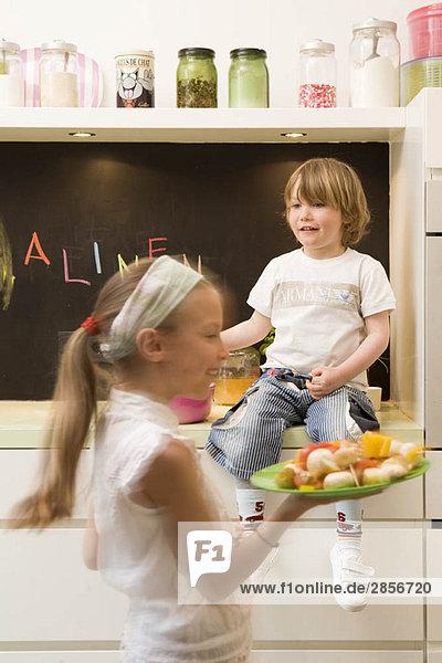 Mädchen und Junge kochen Gemüse
