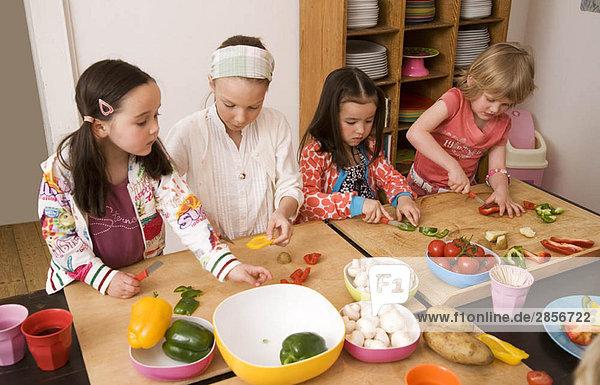 Vier Mädchen schneiden Gemüse