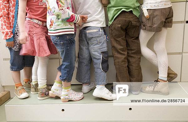 Sechs Paar Mädchen und Jungen Beine