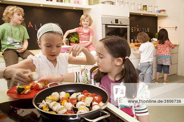 Mädchen und Jungen beim Kochen von Gemüse