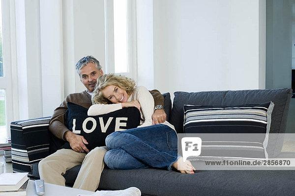 Mann und Frau auf Sofa mit Kissen