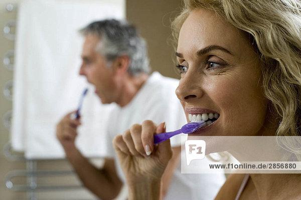 Mann und Frau beim Zähneputzen
