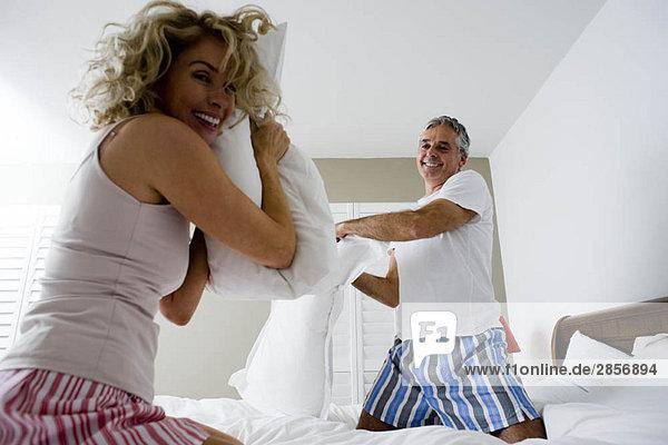 Kissenschlacht zwischen Mann und Frau