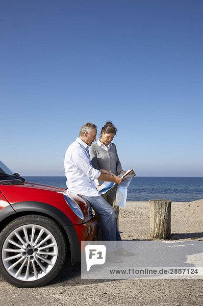 Ein reifes Paar schaut mit dem Auto auf die Karte.