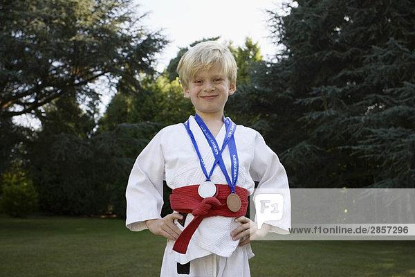Junge im Karate-Kit  mit Medaillen