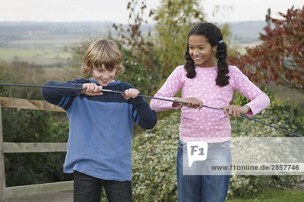 Boy and girl with tent poles