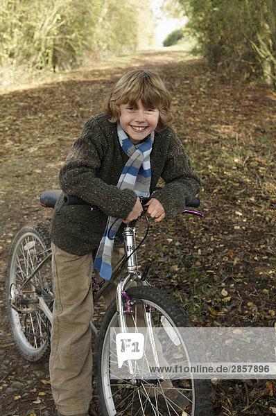 Junge mit Fahrrad auf dem Landweg