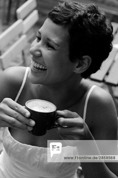 Junge Frau genießt einen Cappuccino