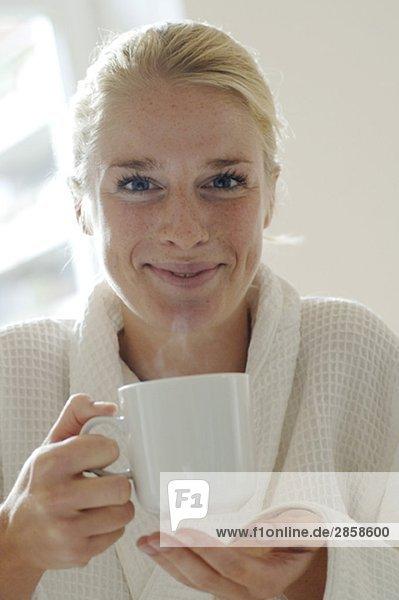 Junge Frau im Bademantel und Kaffeetasse