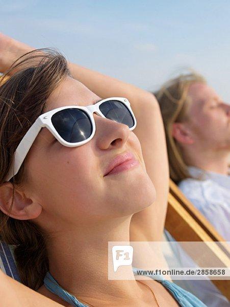 Hübsche junge Frau beim Sonnenbaden mit Sonnenbrille