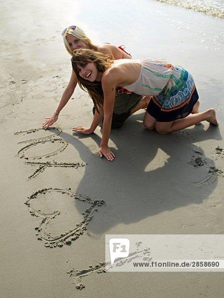Zwei junge Frauen malen in den Sand