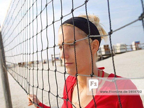 Junge Frau steht Netz des Beachvolleyballnetzes