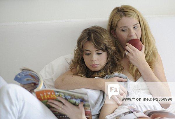 Zwei junge Frauen lesen Zeitschriften und essen einen Apfel
