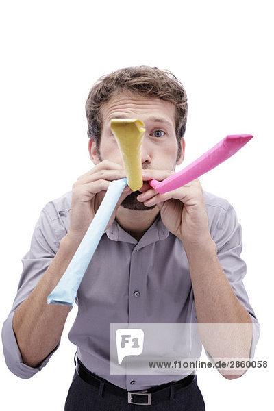 Junger Mann mit Partygebläse im Mund  Portrait