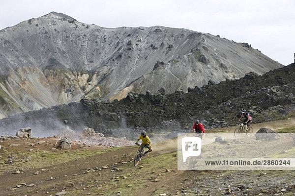 Iceland  Men mountain biking in hilly landscape