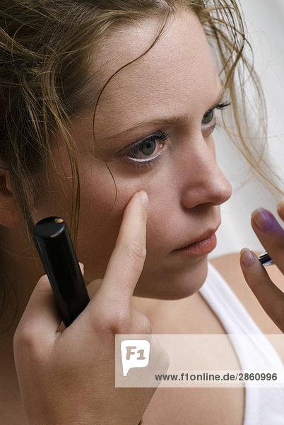 Junge Frau beim Blick in den Handspiegel  Nahaufnahme