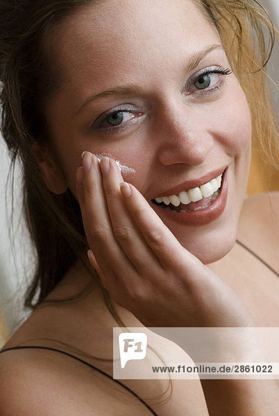 Young woman applying skin cream  close up
