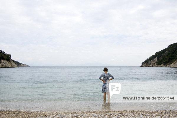Griechenland  Ithaka  Frau beim Waten im Meer  Rückansicht