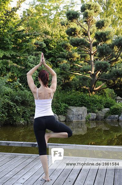 Young woman exercising yoga  rear view