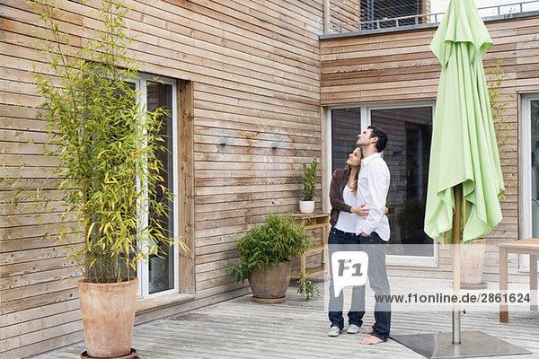 Deutschland  Bayern  München  Paar auf Terrasse vor dem Haus