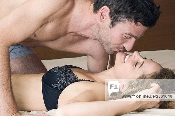 Junges Paar  das sich im Bett küsst