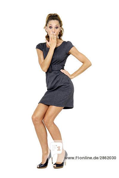 Junge Frau im Minikleid stehend mit Hand über dem Mund  Portrait