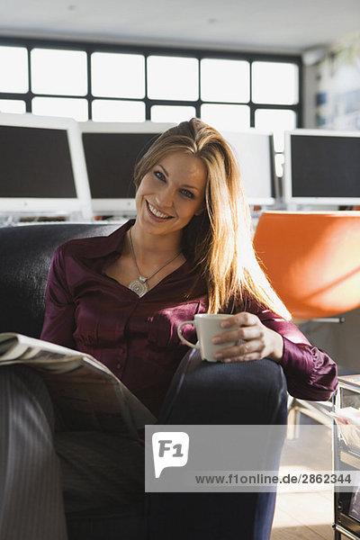 Geschäftsfrau im Büro mit Becher und Zeitung  Porträt