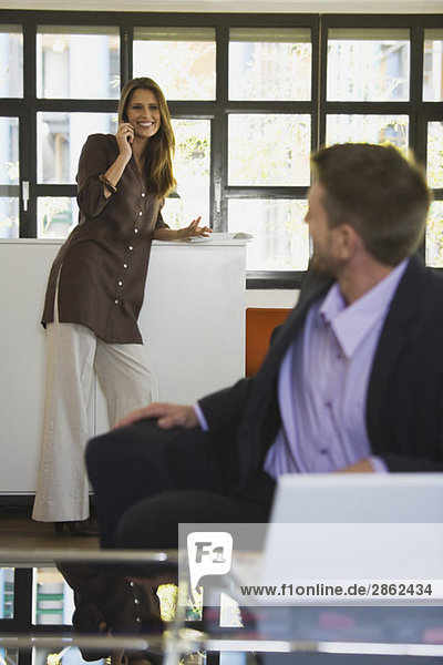 Frau im Büro mit Handy  Mann im Vordergrund