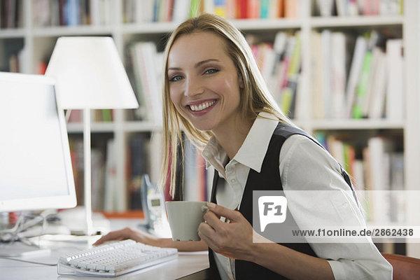 Junge Frau im Amt mit einer Tasse Kaffee  lächelnd  Porträt