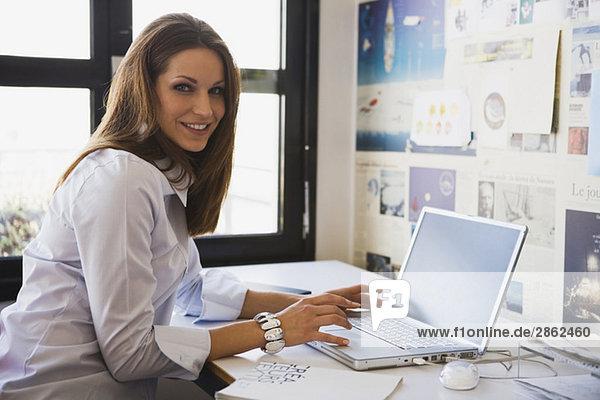 Junge Frau im Büro mit Laptop  Portrait
