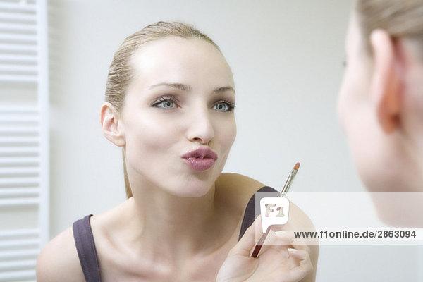 Junge Frau hält Lippenbürste  Lippen verziehen  Mund