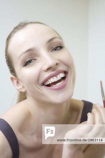 Junge Frau mit Lippenpinsel  lachend  Portrait  Nahaufnahme