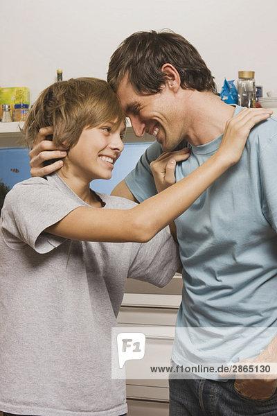 Vater umarmt Sohn (14-15) in der Küche  lächelnd