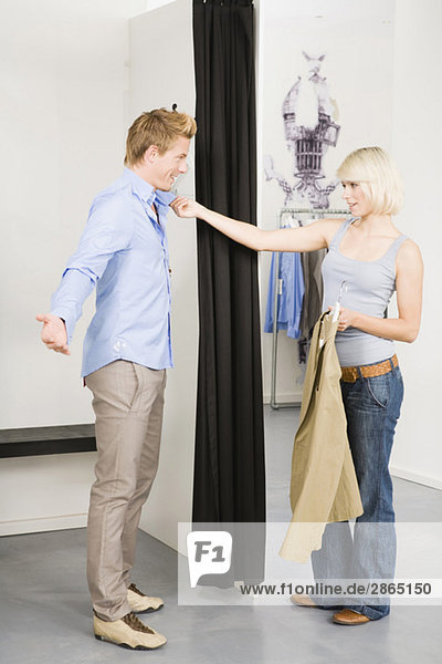 Couple in changing room  woman holding man's collar