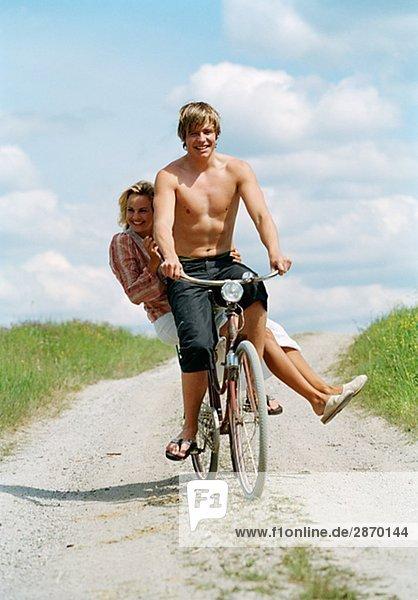 Ein junger Mann und eine junge Frau auf dem Fahrrad am sonnigen Tag Schweden.