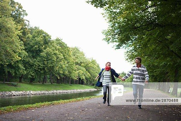 Ein paar laufen Hand in Hand im Park Schweden.