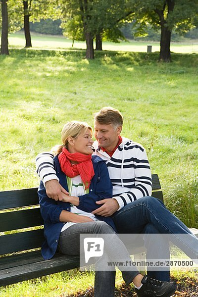 Ein paar auf einer Bank im Park Schweden sitzen.