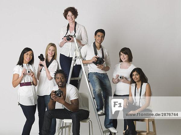 Gruppenportrait von jungen Fotografen die auf Leitern und Stühlen sitzen